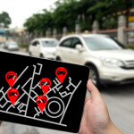 Car sharing service or rental concept. Sharing economy and collaborative consumption. Man hand holding tablet with icons application screen and blur car park background.